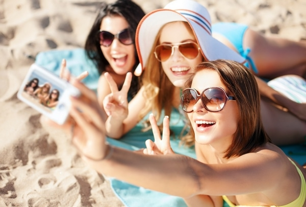 Group of girls taking a picture on the beach on summer vacation